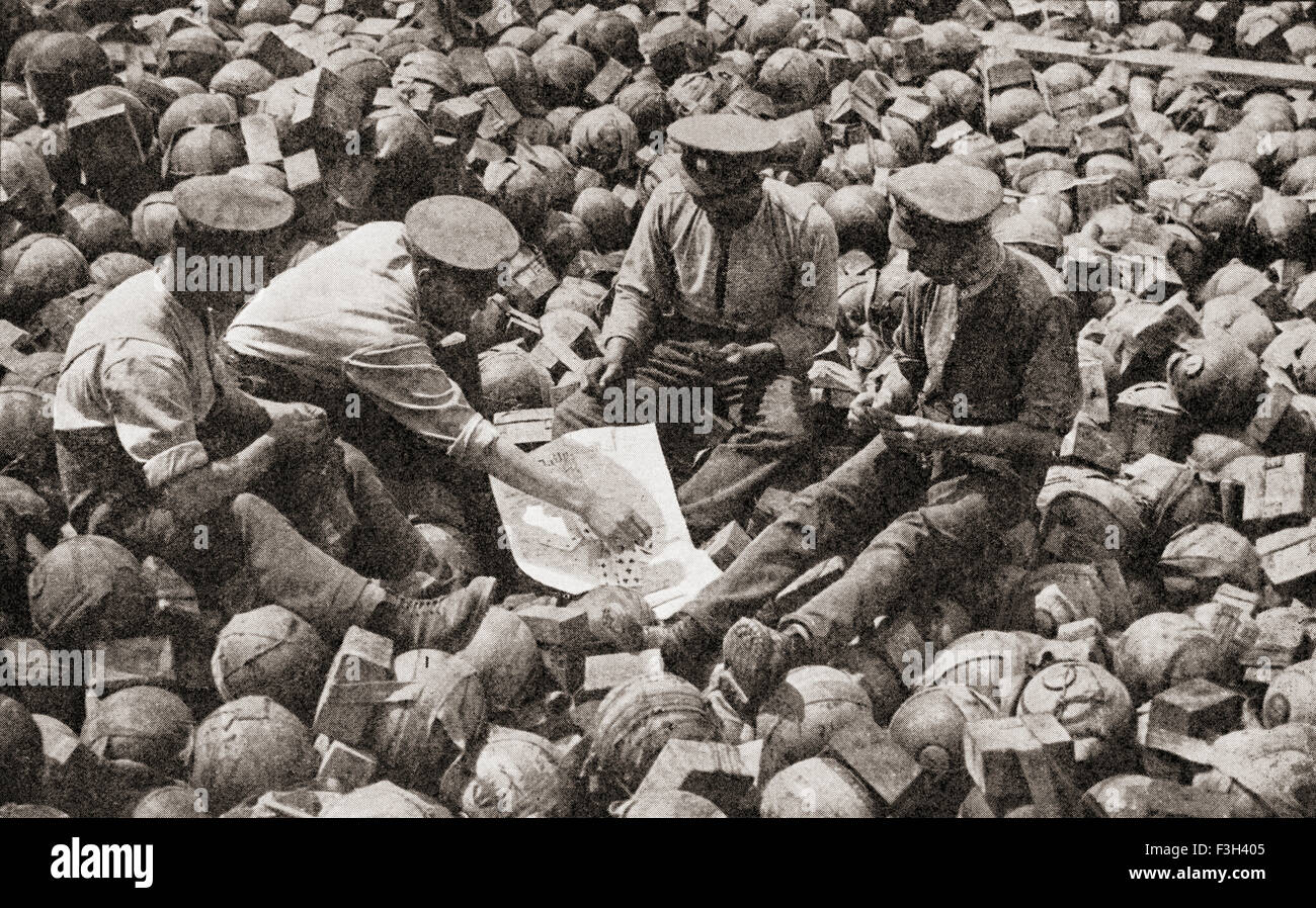 British soldiers, sat on captured German equipment, playing a game of cards during WWI. - Stock Image