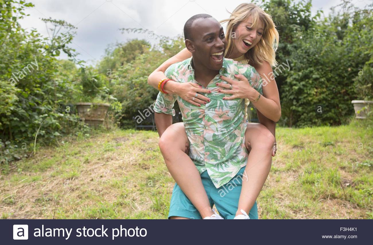 Couple playing piggy-back in garden - Stock Image