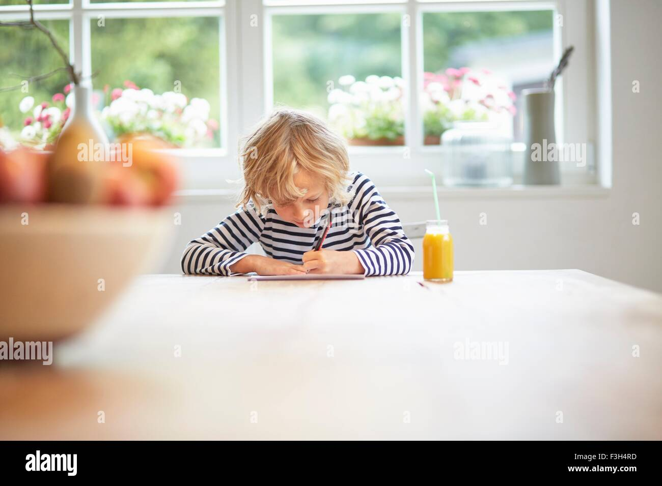 Young boy sitting at table, writing - Stock Image
