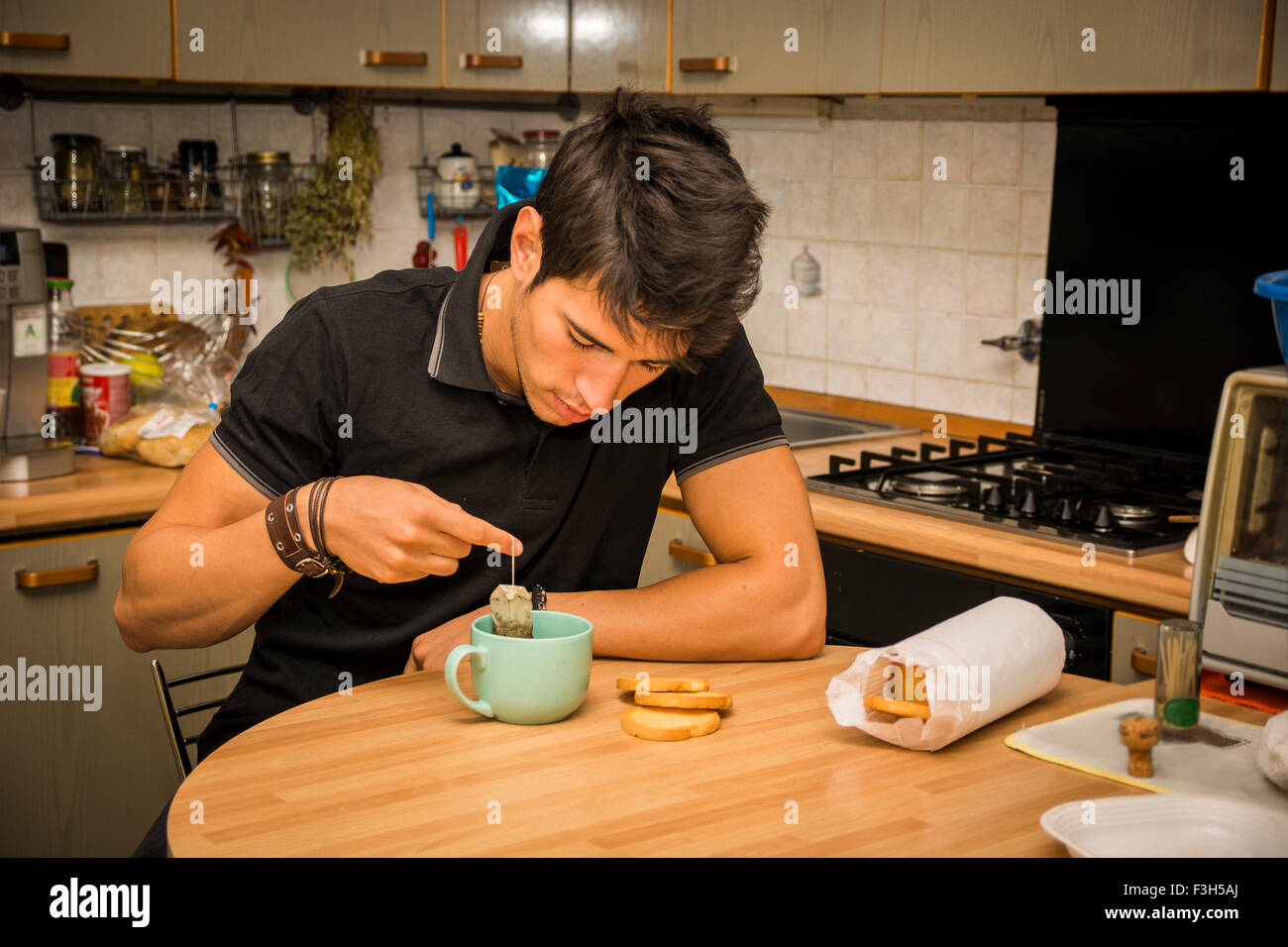Tired or Sick Attractive Young Man Leaning with Elbow on Kitchen Table and Holding Cup of Coffee for Breakfast - Stock Image