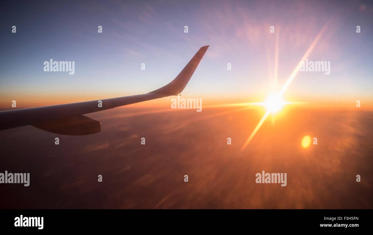 Wing of plane seen from aeroplane window, at sunset - Stock Image