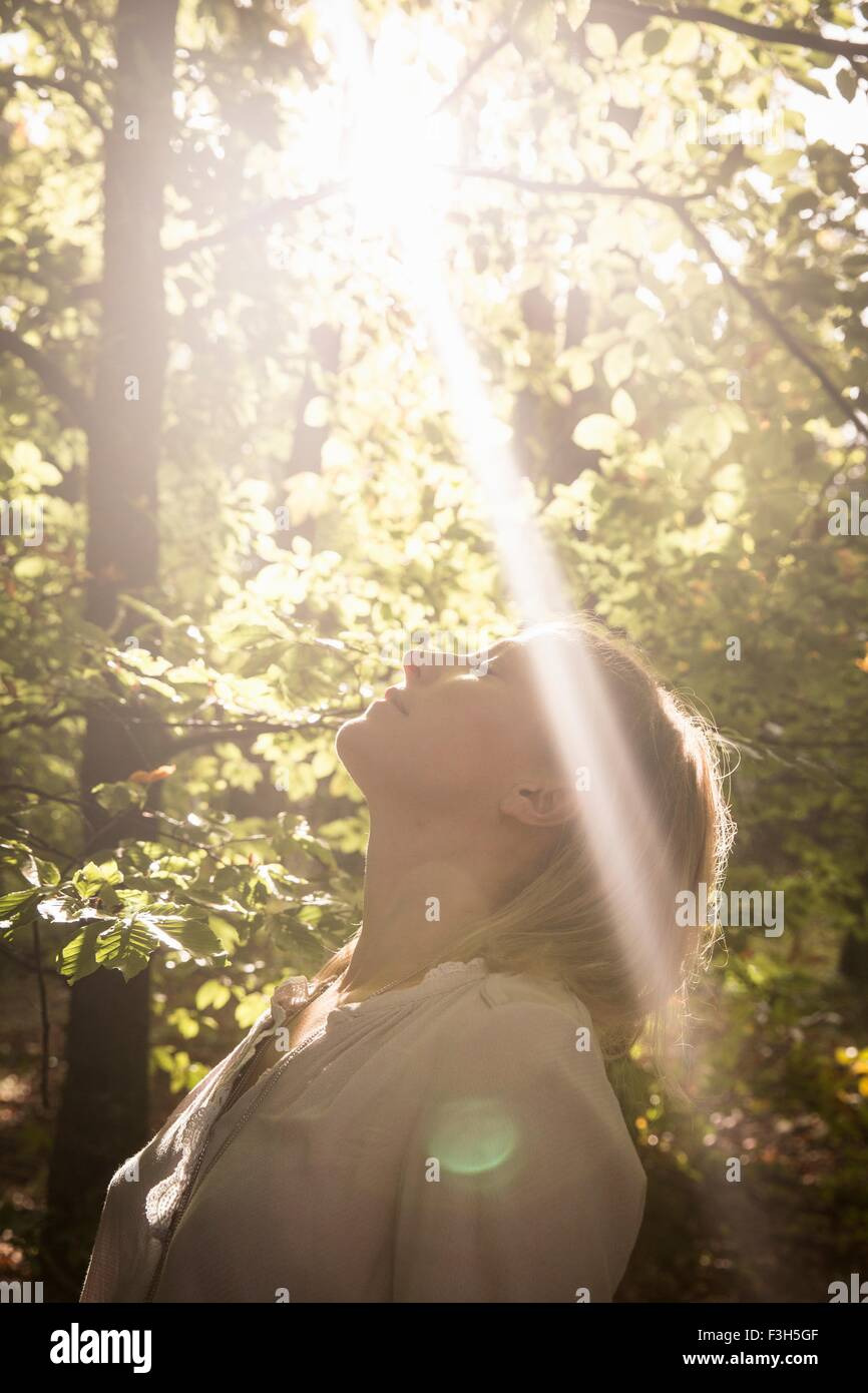 Mature woman standing in stream of light in forest - Stock Image