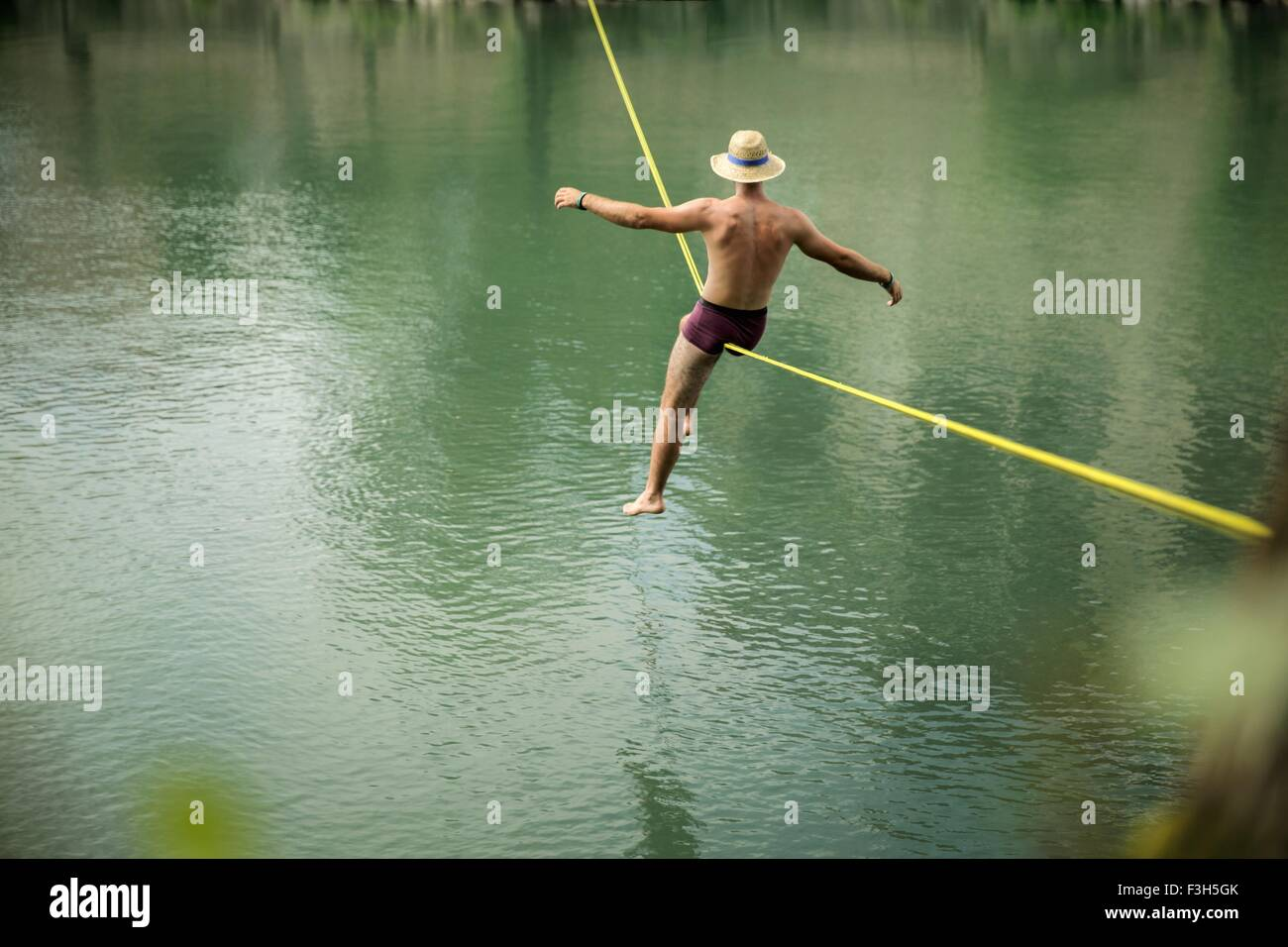 Mature man balancing on rope over lake, rear view - Stock Image