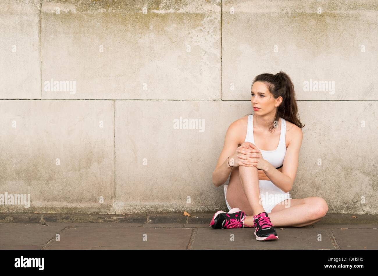Young female runner sitting on sidewalk looking sideways - Stock Image