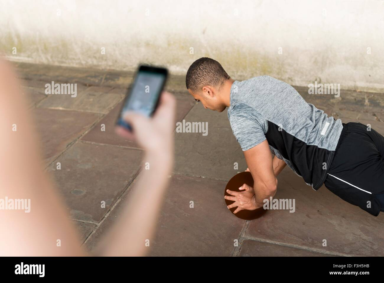 Over shoulder view of trainer timing male runners push ups on smartphone - Stock Image