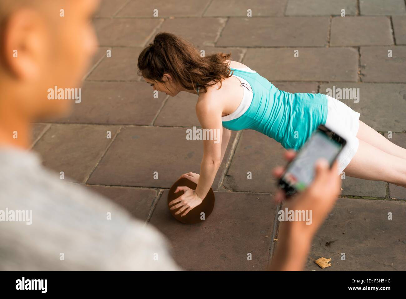 Over shoulder view of trainer timing female runners push ups on smartphone - Stock Image