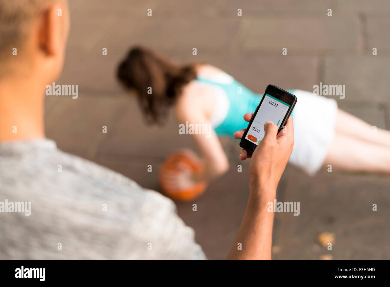 Over shoulder view of male trainer timing female runners push ups on smartphone - Stock Image
