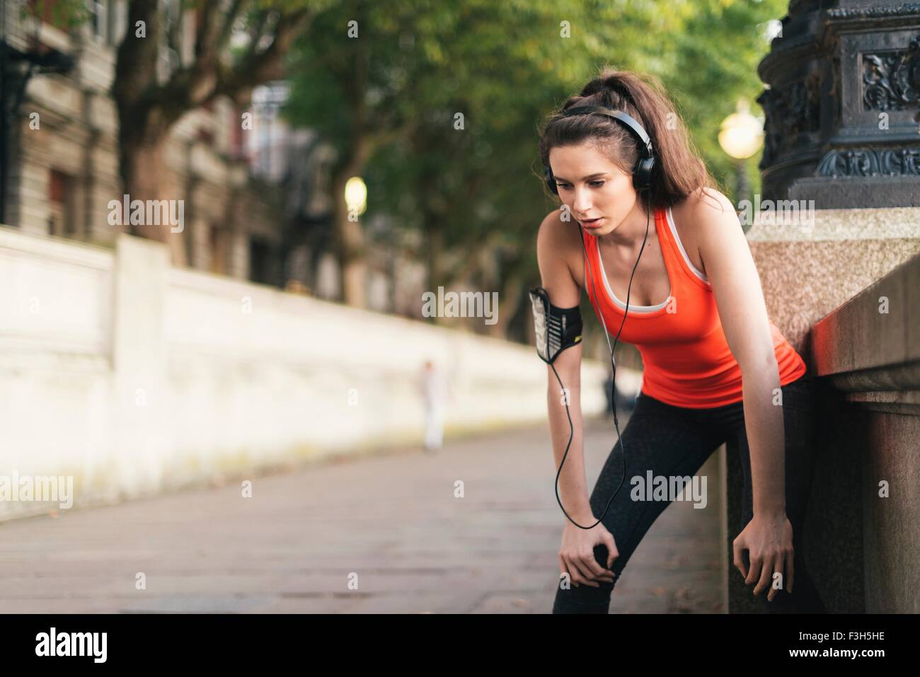 Female runner wearing headphones taking a break on riverside - Stock Image