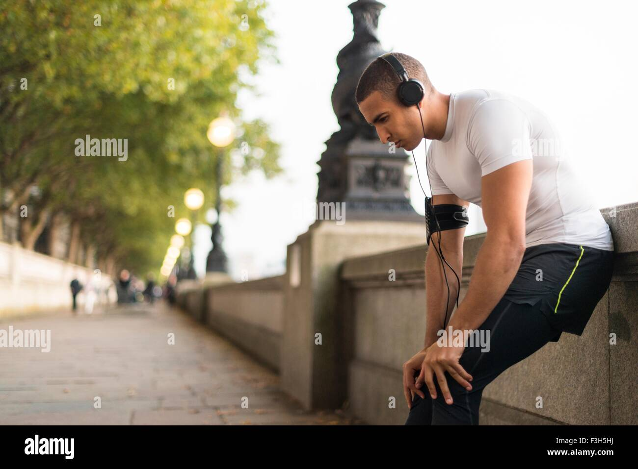 Young male runner wearing headphones taking a break on riverside - Stock Image