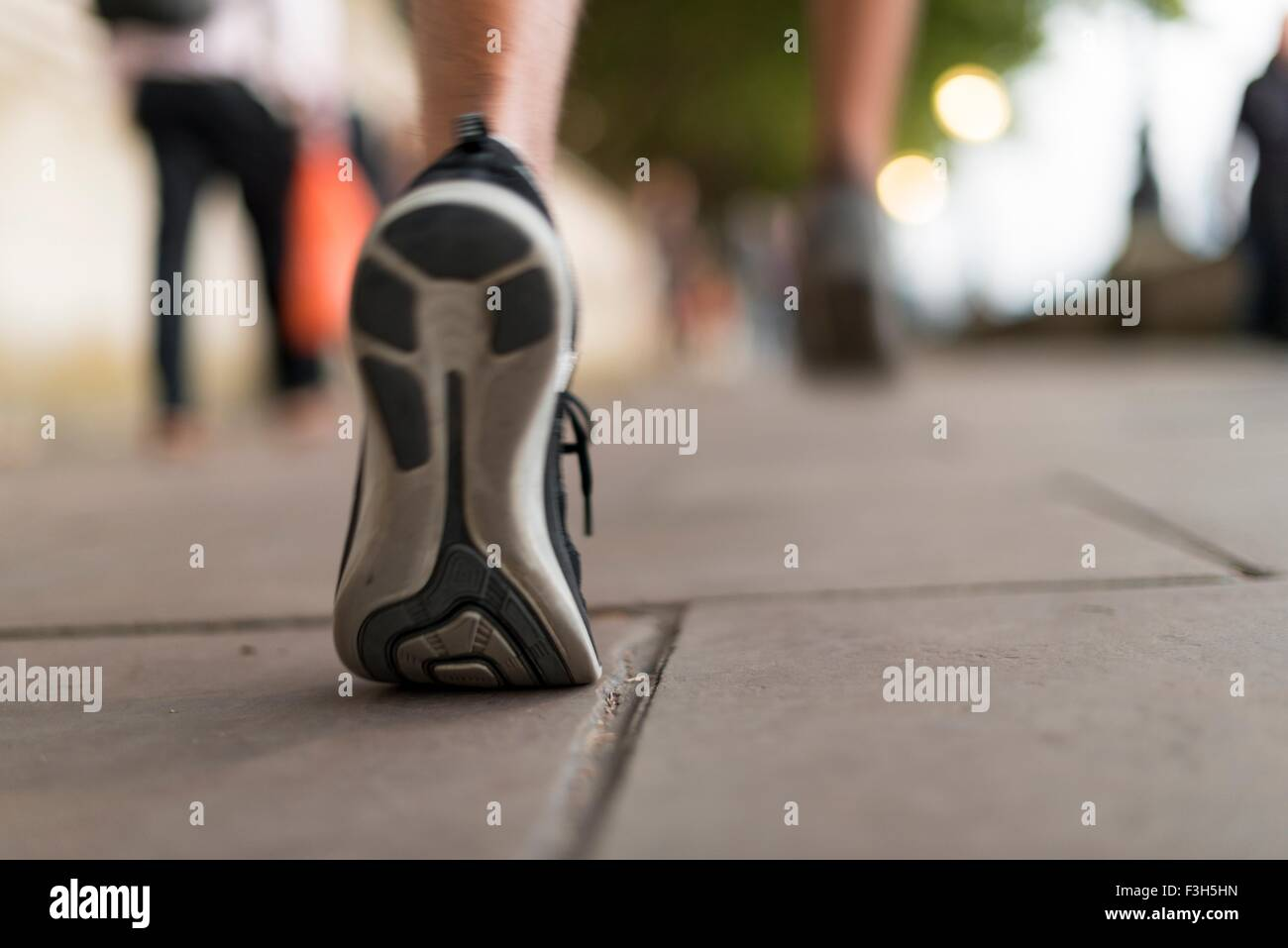 Close up of male runners trainers running on sidewalk - Stock Image