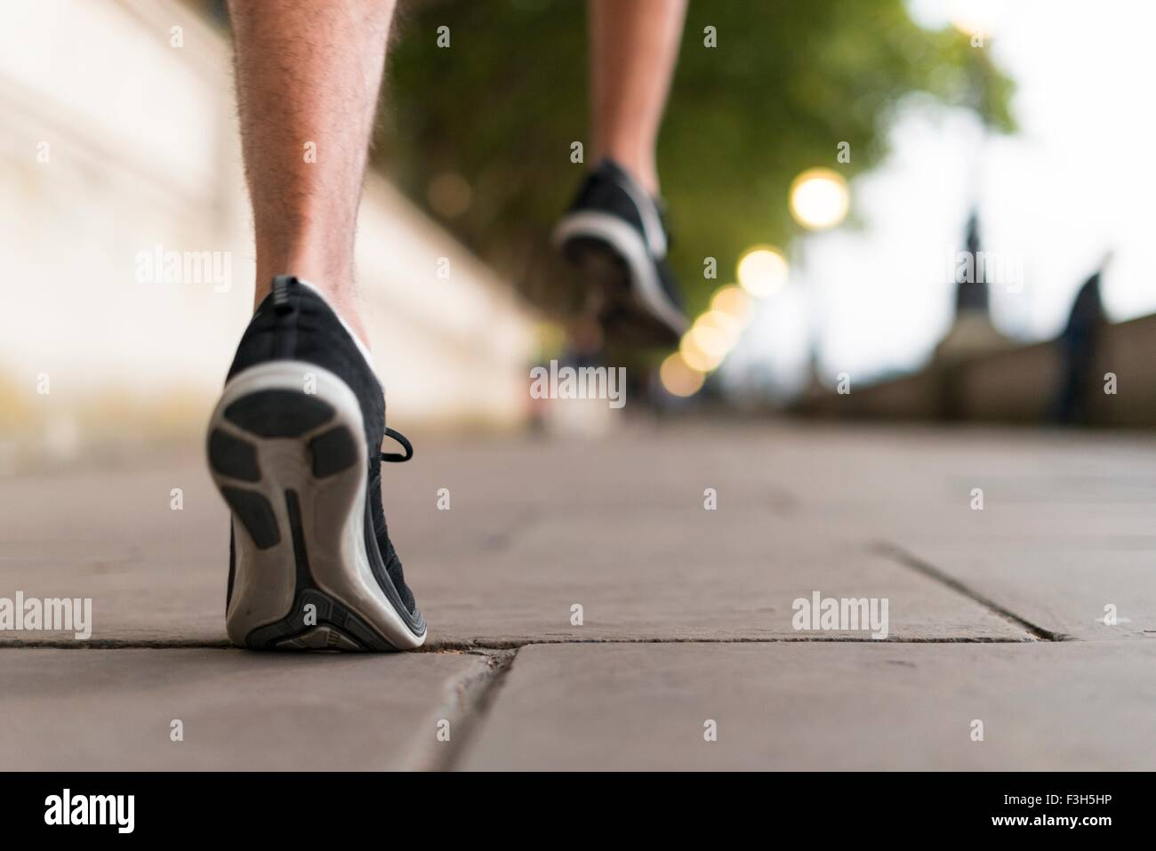 Young male runners wearing trainers running on sidewalk - Stock Image