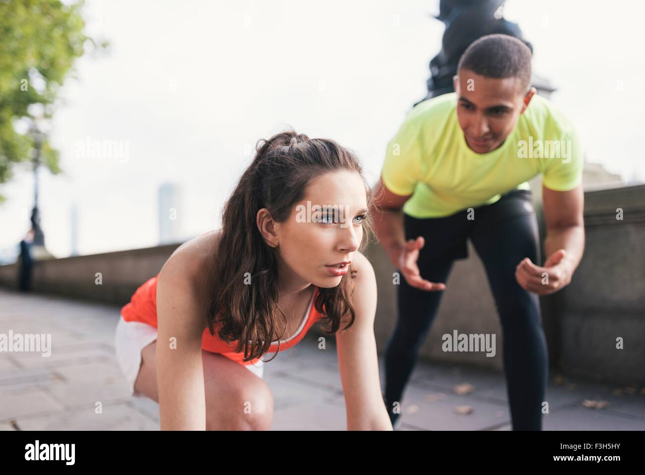 Young male trainer encouraging female runner  on riverbank - Stock Image
