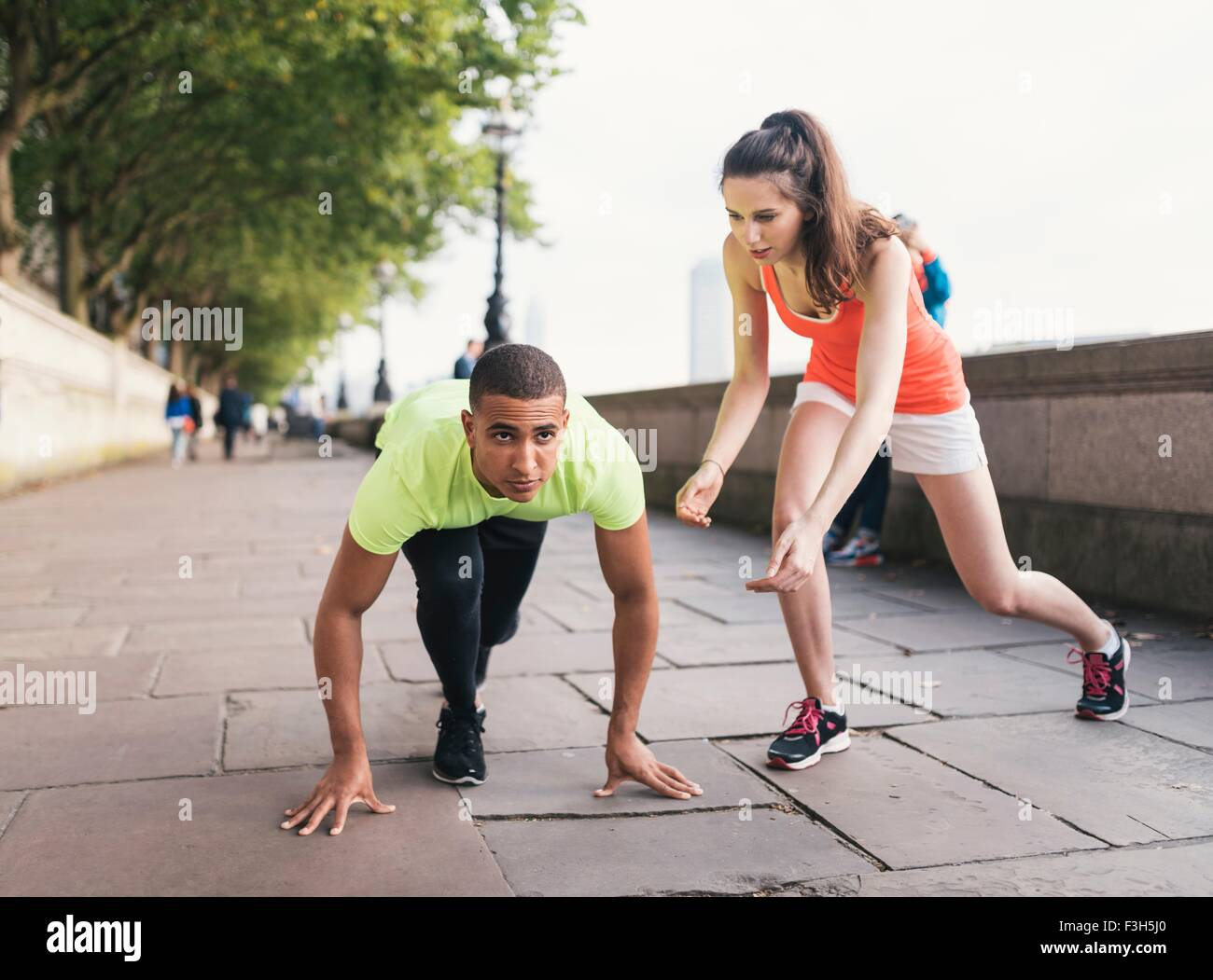 Young female trainer encouraging male runner  on riverbank - Stock Image