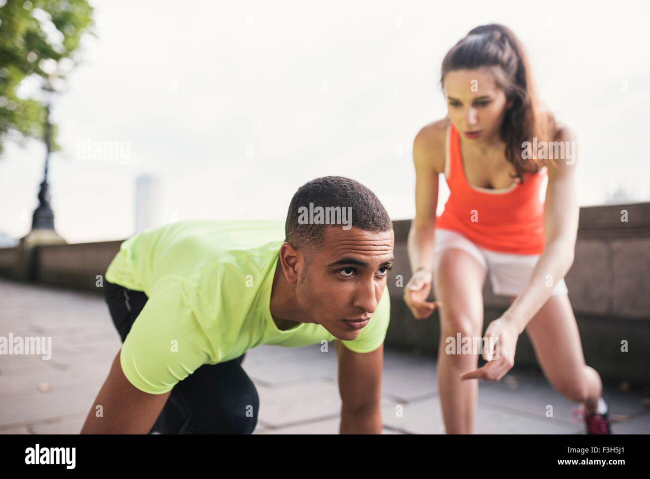 Young female trainer with male runner on riverbank - Stock Image