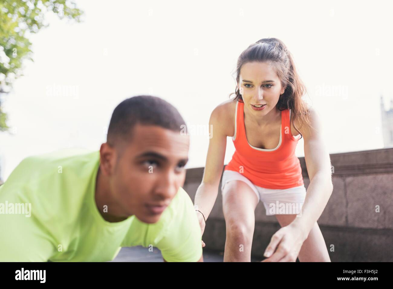 Young female trainer practicing starts with male runner - Stock Image