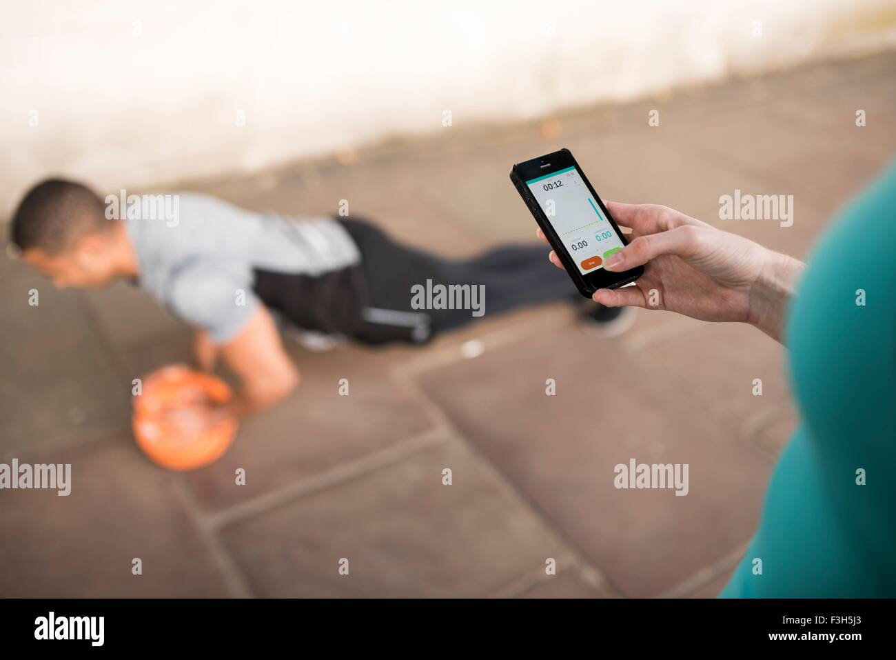 Over shoulder view of female trainer timing male runners push ups on smartphone - Stock Image