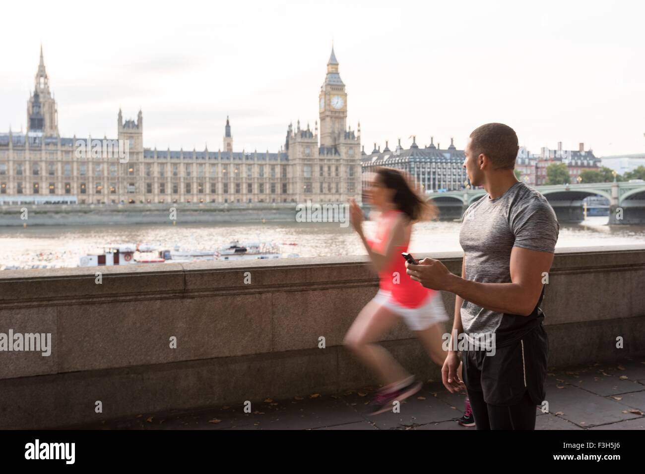 Male trainer timing female runner on Southbank, London, UK - Stock Image