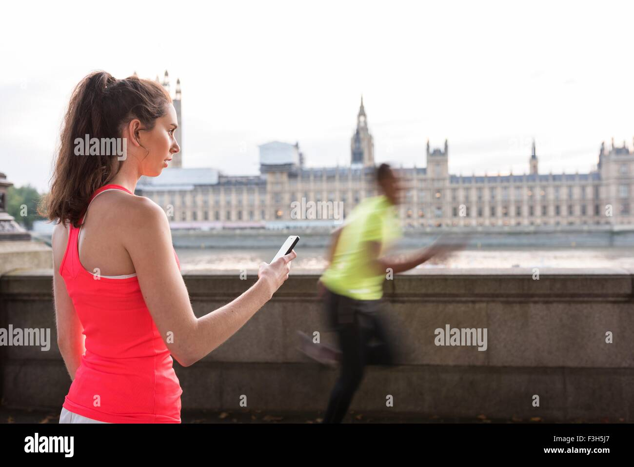 Female trainer timing male runner on Southbank, London, UK - Stock Image