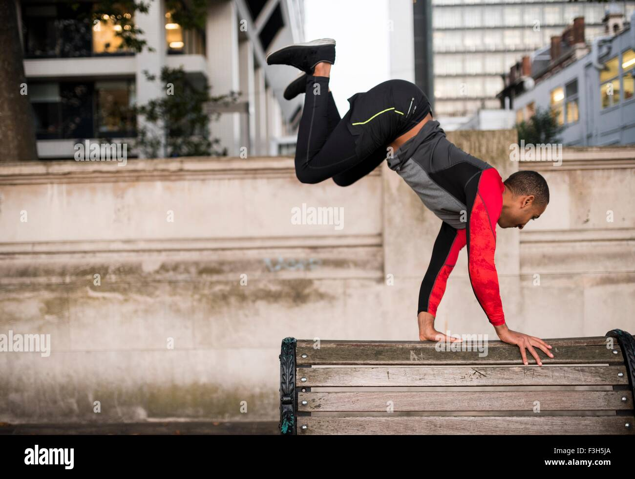 Young man jumping over park bench in city - Stock Image