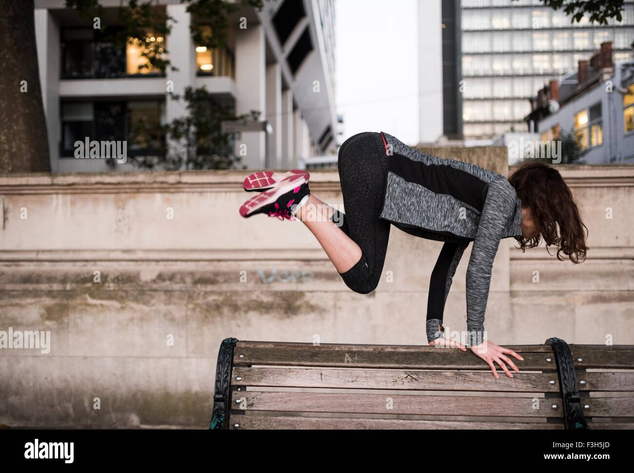 Young woman jumping over park bench in city - Stock Image