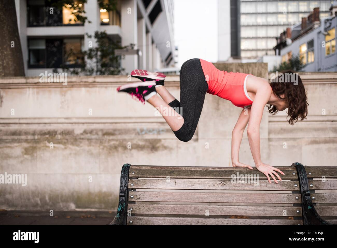 Young woman leaping over park bench in city - Stock Image