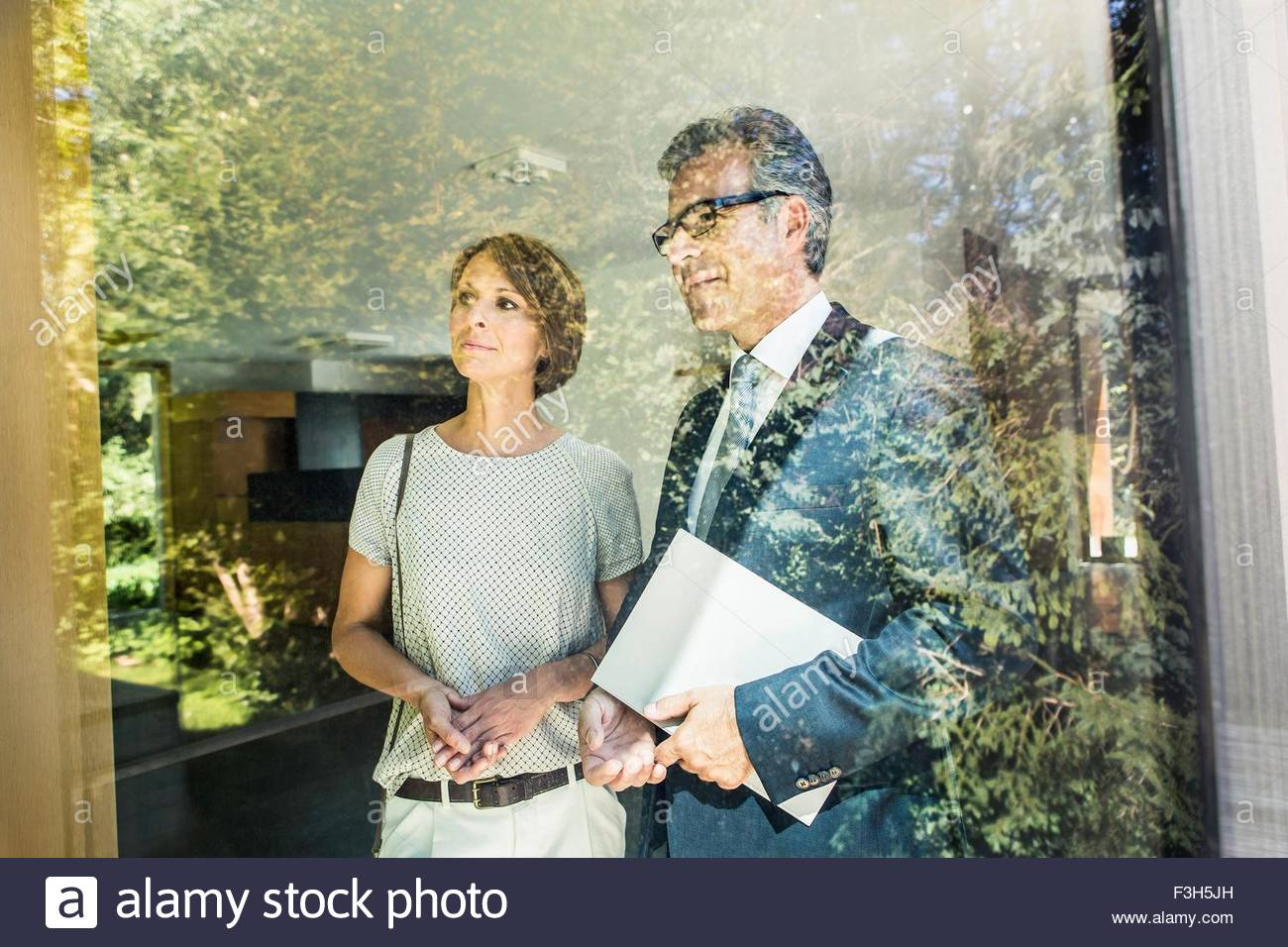 Mature woman looking at new house with estate agent - Stock Image