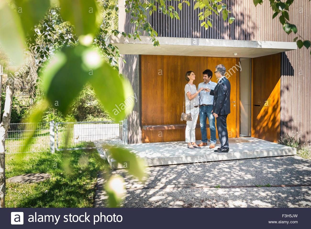 Estate agent handing keys to mature couple outside new house - Stock Image
