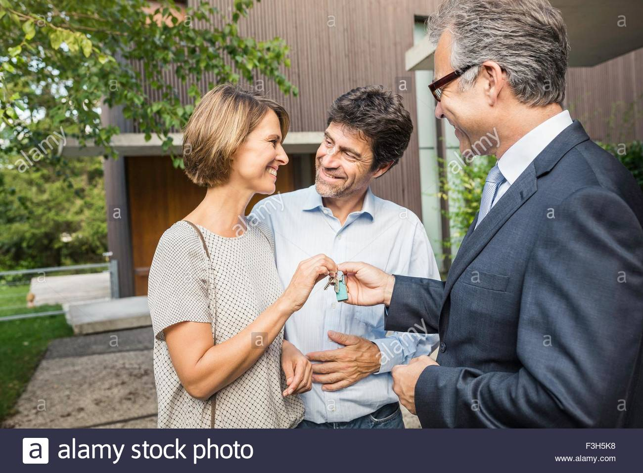 Estate agent handing keys to mature couple at new house Stock Photo