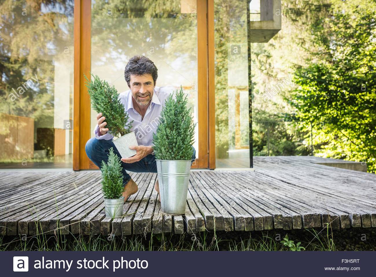 Portrait of mature man with pot plants outside new house - Stock Image