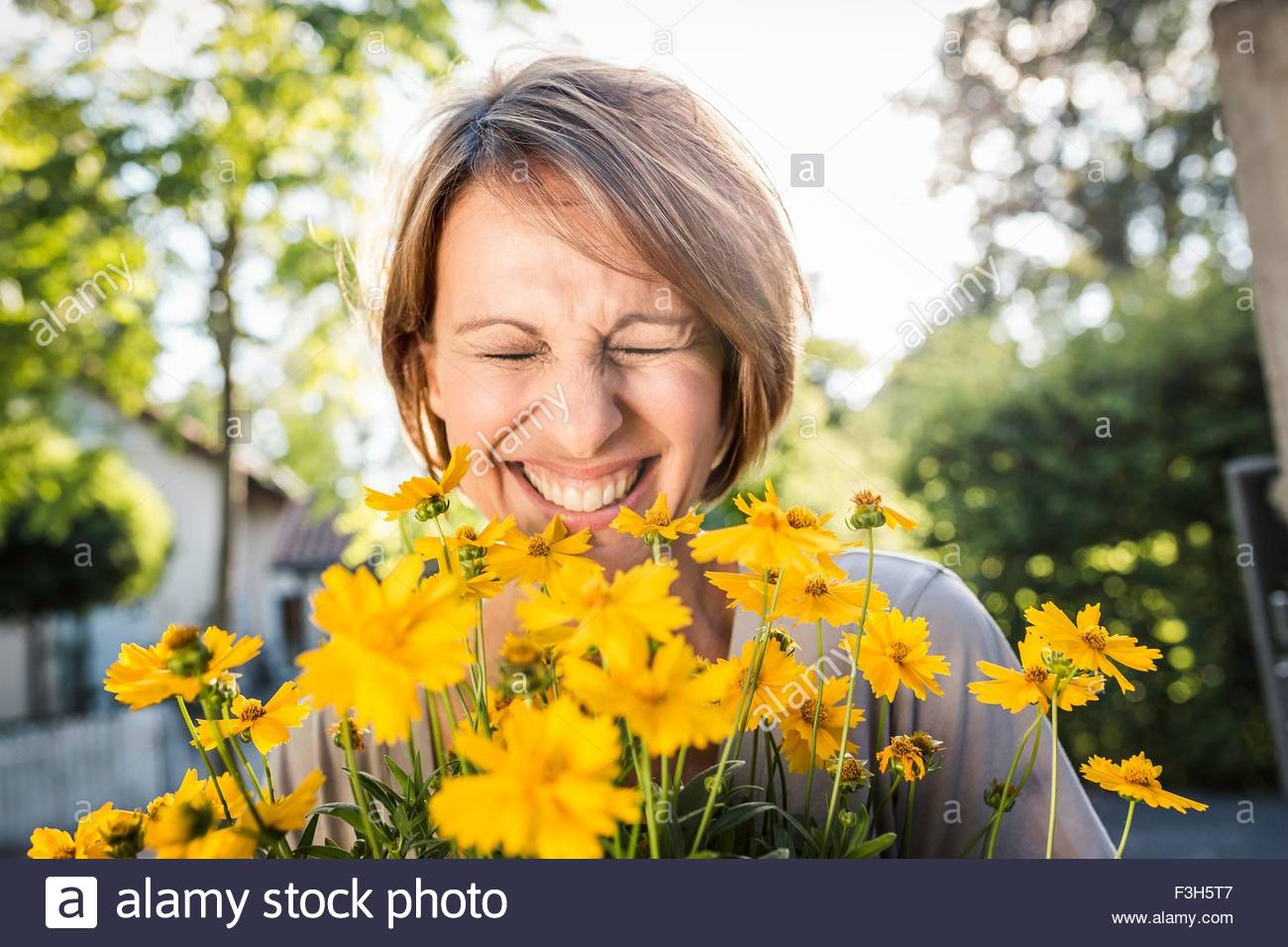 Portrait of mature woman with yellow flowers - Stock Image