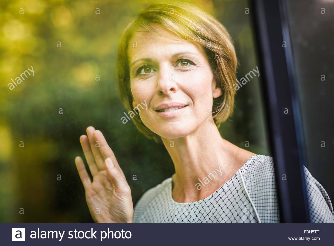 Mature woman looking through window of new house - Stock Image