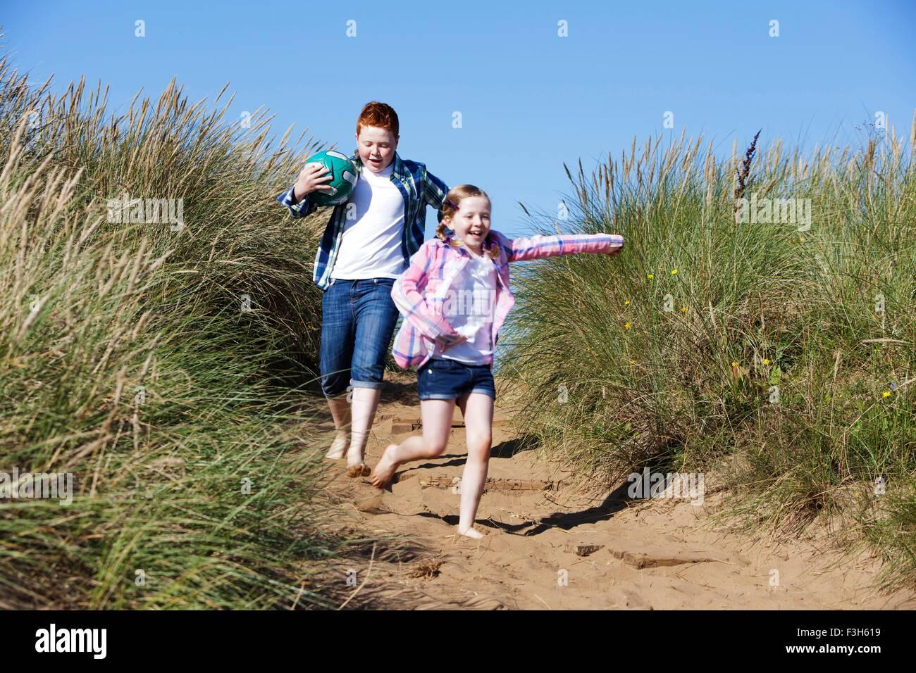 Girl and boy running through marram grass holding football smiling - Stock Image