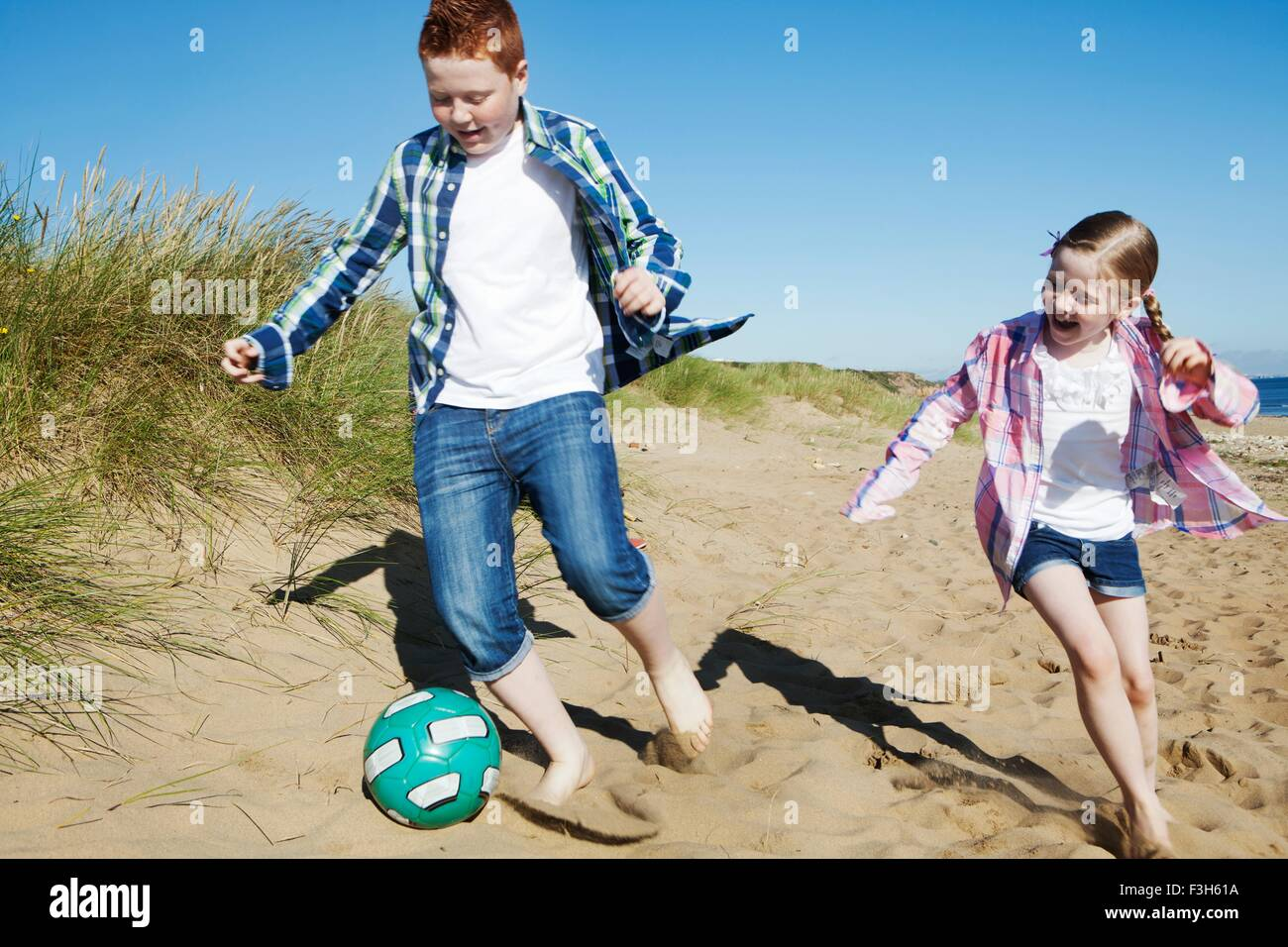 Girl and boy chasing football across sand, smiling Stock Photo