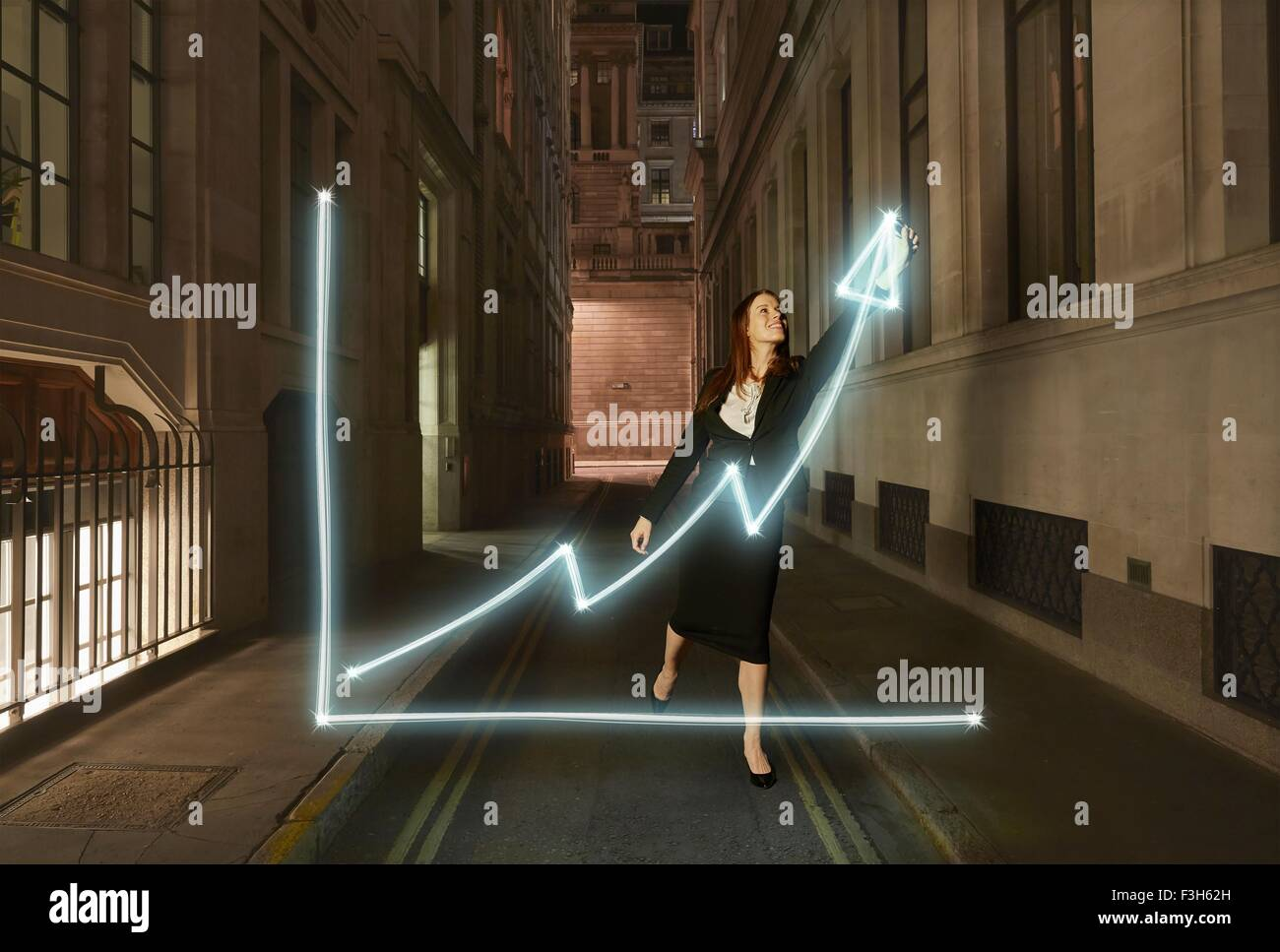 Businesswoman light painting glowing chart with upward arrow symbol  on city street at night - Stock Image
