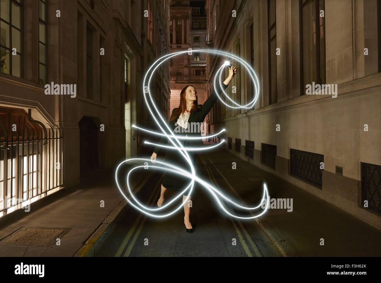 Businesswoman light painting glowing pound sign on city street at night - Stock Image