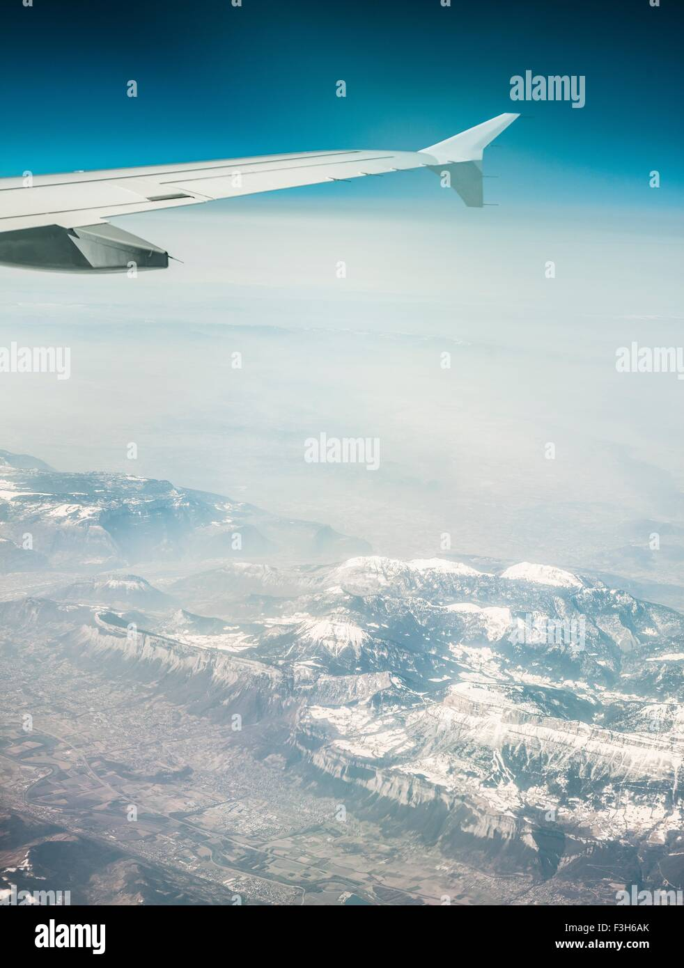 Aerial view of airplane wing and misty snow capped mountains - Stock Image