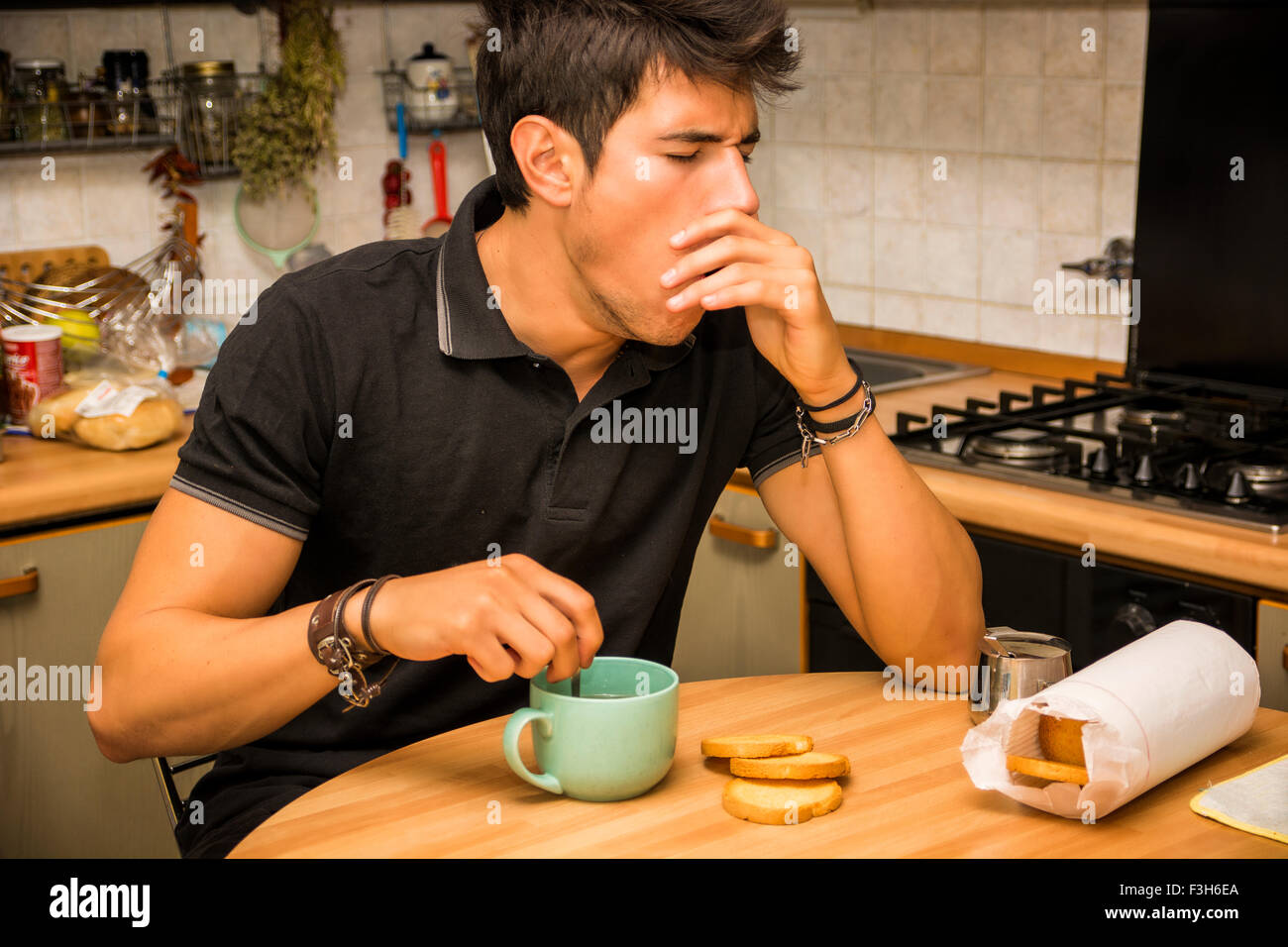 Tired Attractive Young Man Yawning with Eyes Closed and Hand on Mouth, Leaning with Elbow on Kitchen Table and Holding - Stock Image