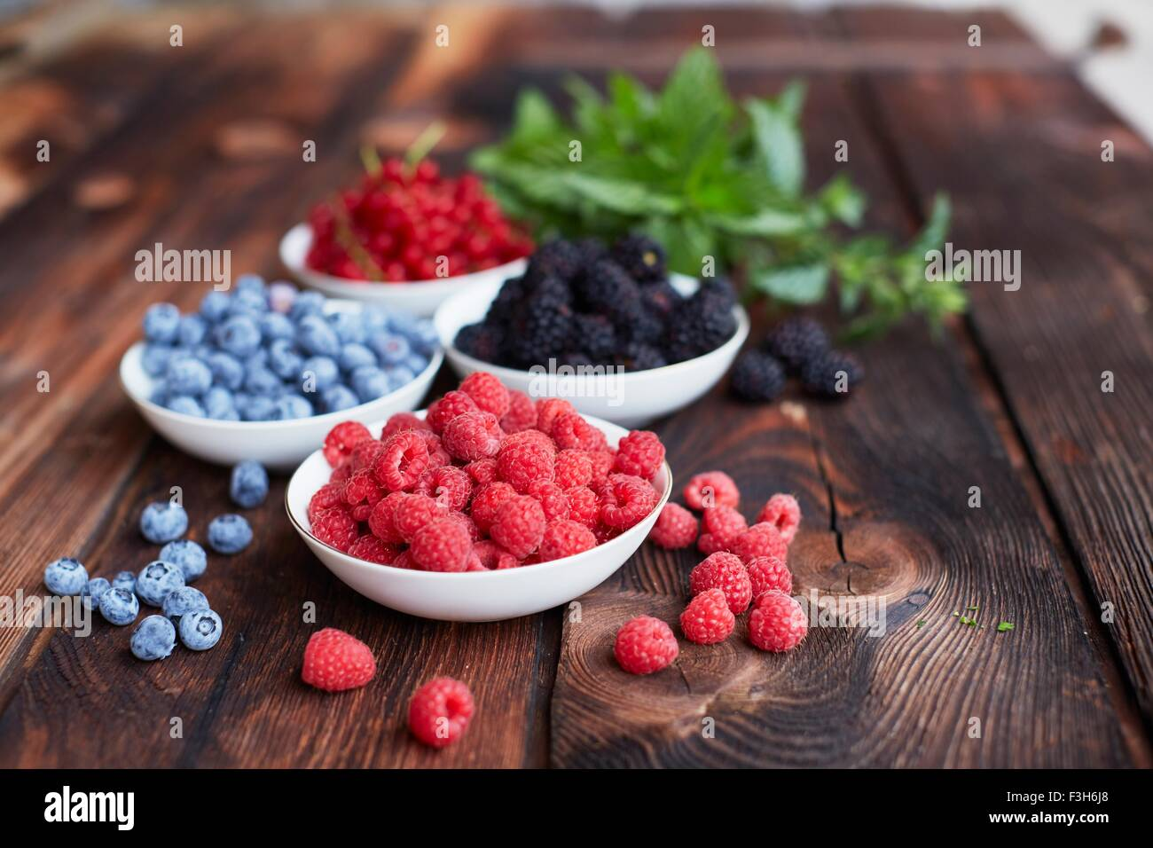 Picnic table with four bowls of fresh berries - Stock Image