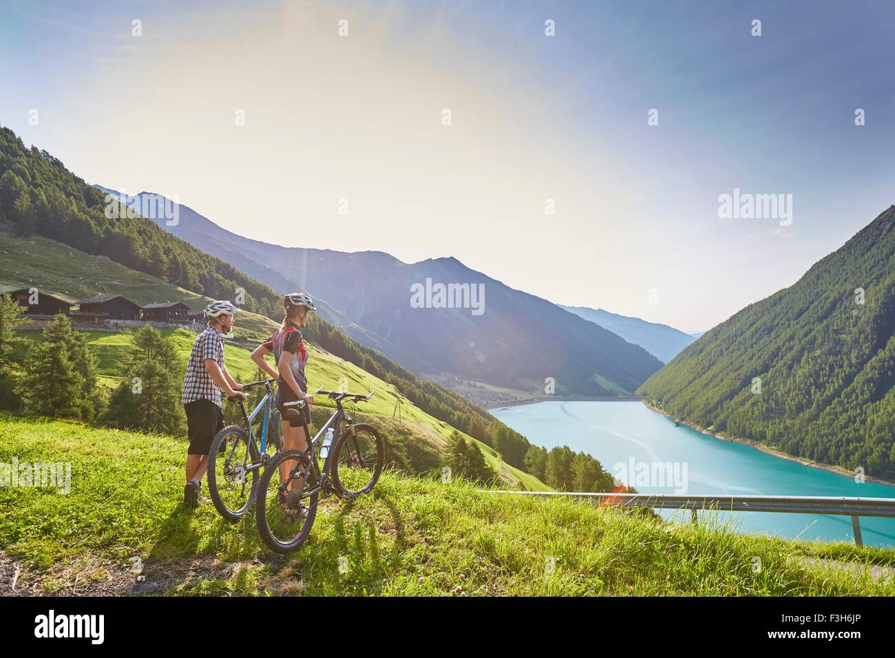 Young mountain biking couple looking out over Vernagt reservoir and Finailhof farmhouse, Val Senales, South Tyrol, - Stock Image