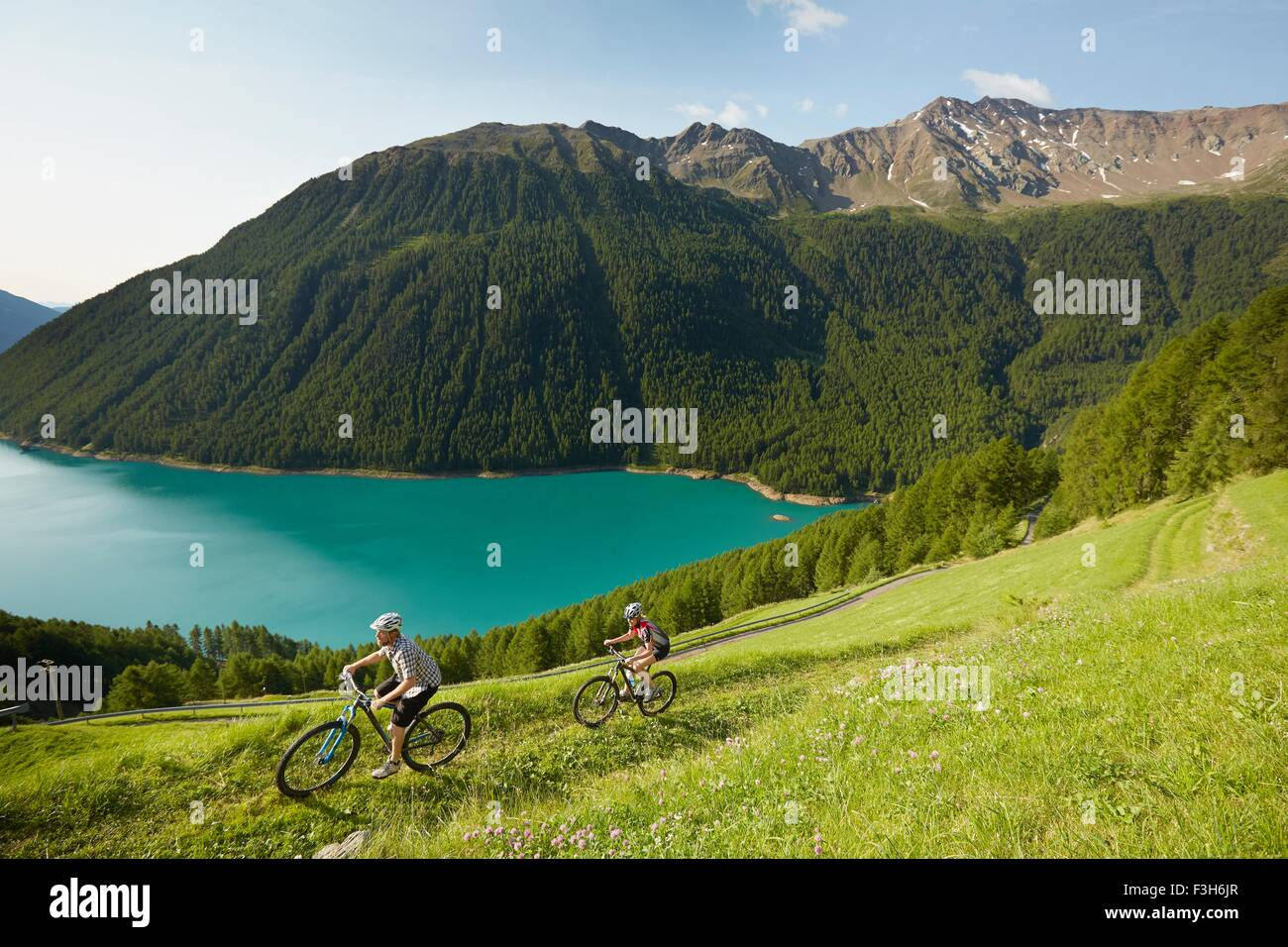 Young couple mountain biking at Vernagt reservoir, Val Senales, South Tyrol, Italy - Stock Image