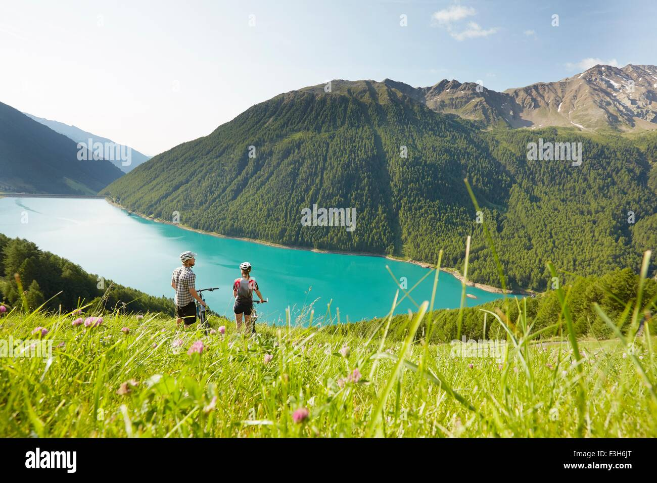 Young couple on mountain bikes looking out at Vernagt reservoir, Val Senales, South Tyrol, Italy - Stock Image