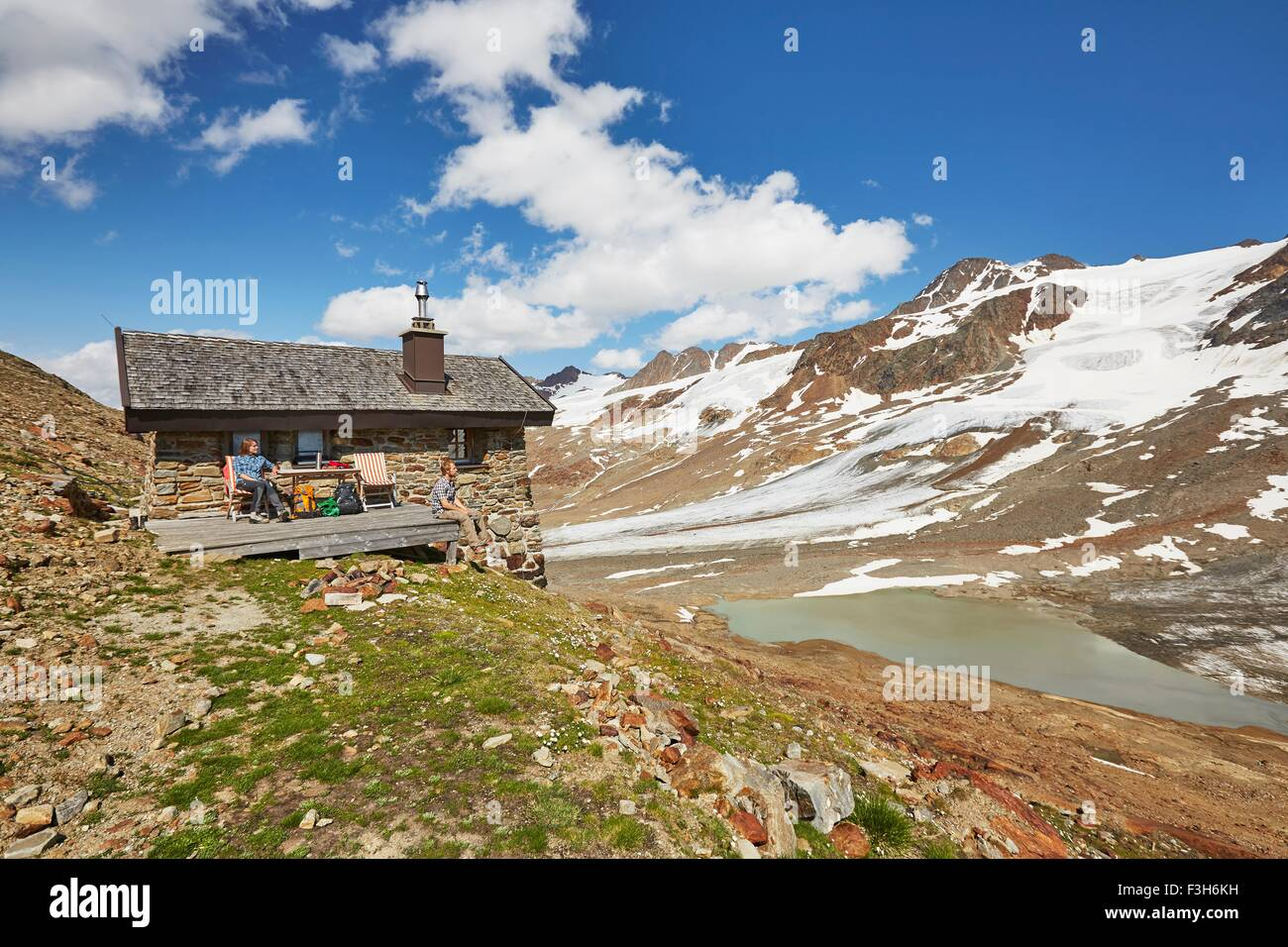 Young hiking couple taking a break outside hut, Val Senales Glacier, Val Senales, South Tyrol, Italy Stock Photo