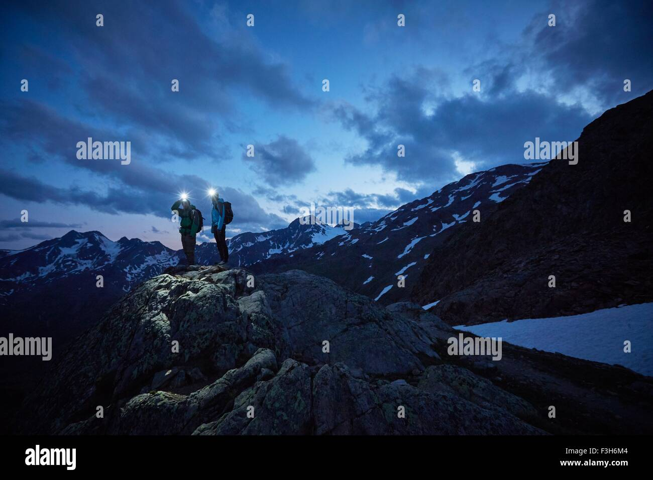 Young hiking couple looking out over rugged mountains at night, Val Senales Glacier, Val Senales, South Tyrol, Italy - Stock Image