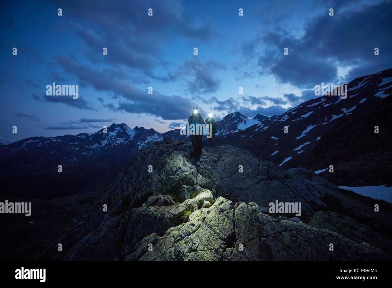 Young couple hiking at night wearing headlamps, Val Senales Glacier, Val Senales, South Tyrol, Italy - Stock Image