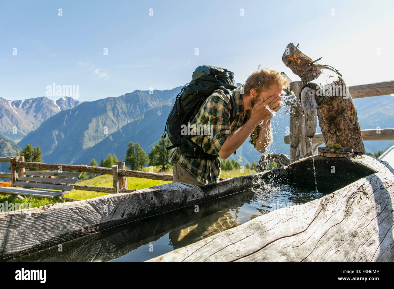 Young male hiker washing face in rustic trough, Karthaus, Val Senales, South Tyrol, Italy - Stock Image