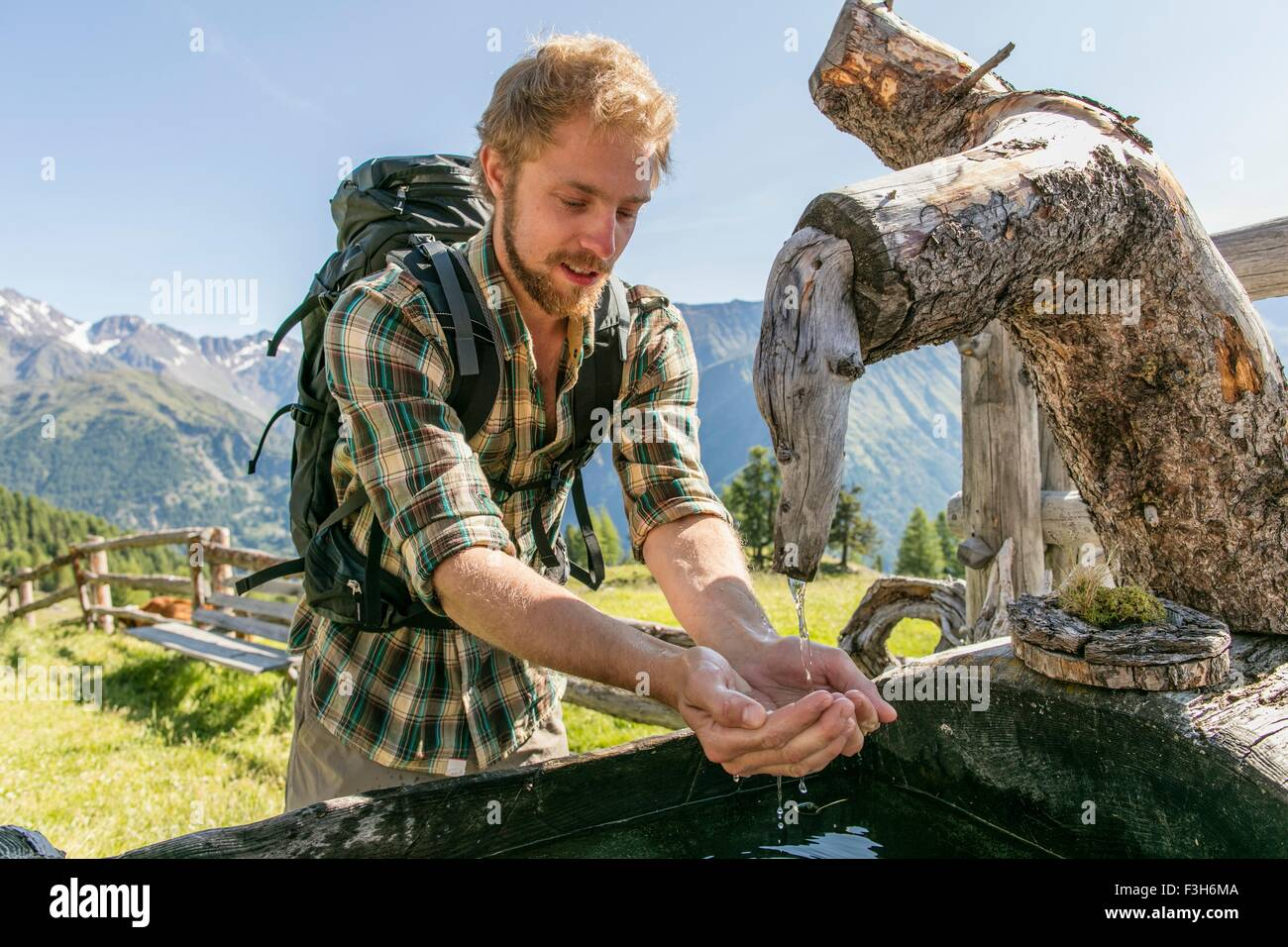 Young male hiker drinking water from rustic trough, Karthaus, Val Senales, South Tyrol, Italy - Stock Image