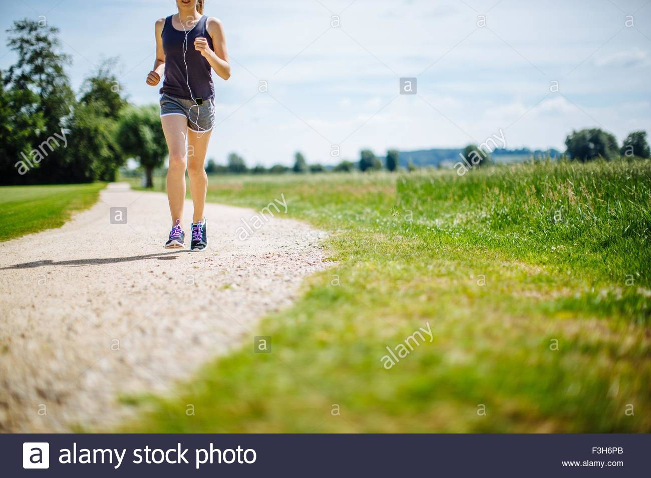 Young girl in park, running on pathway, low section Stock Photo