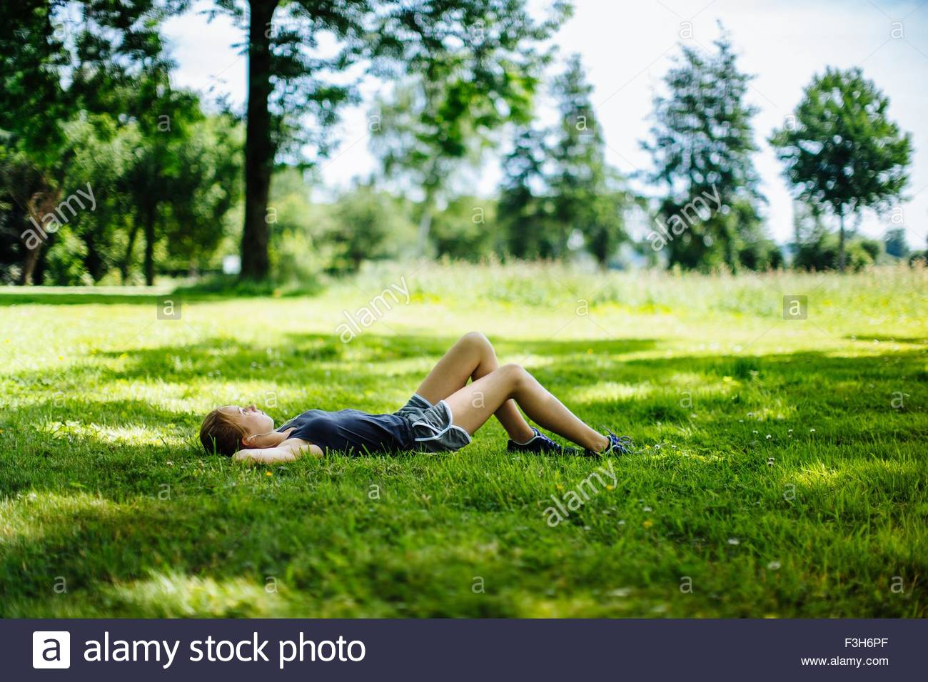 Young girl in park, lying on grass, relaxing - Stock Image