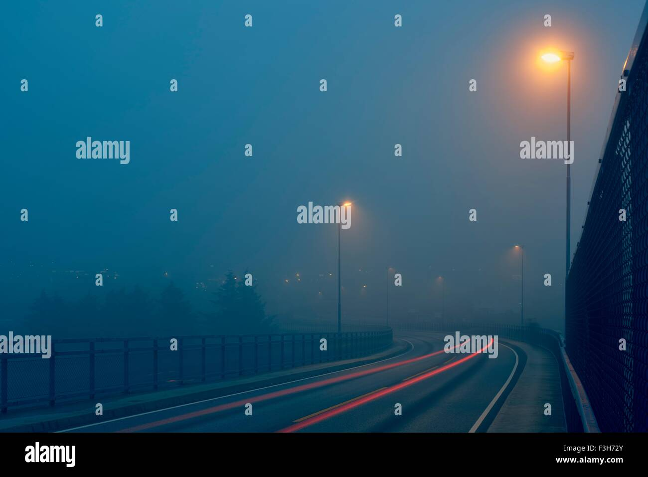 Diminishing perspective of light trails on misty road illuminated by street lights, Haugesund, Rogaland County, - Stock Image