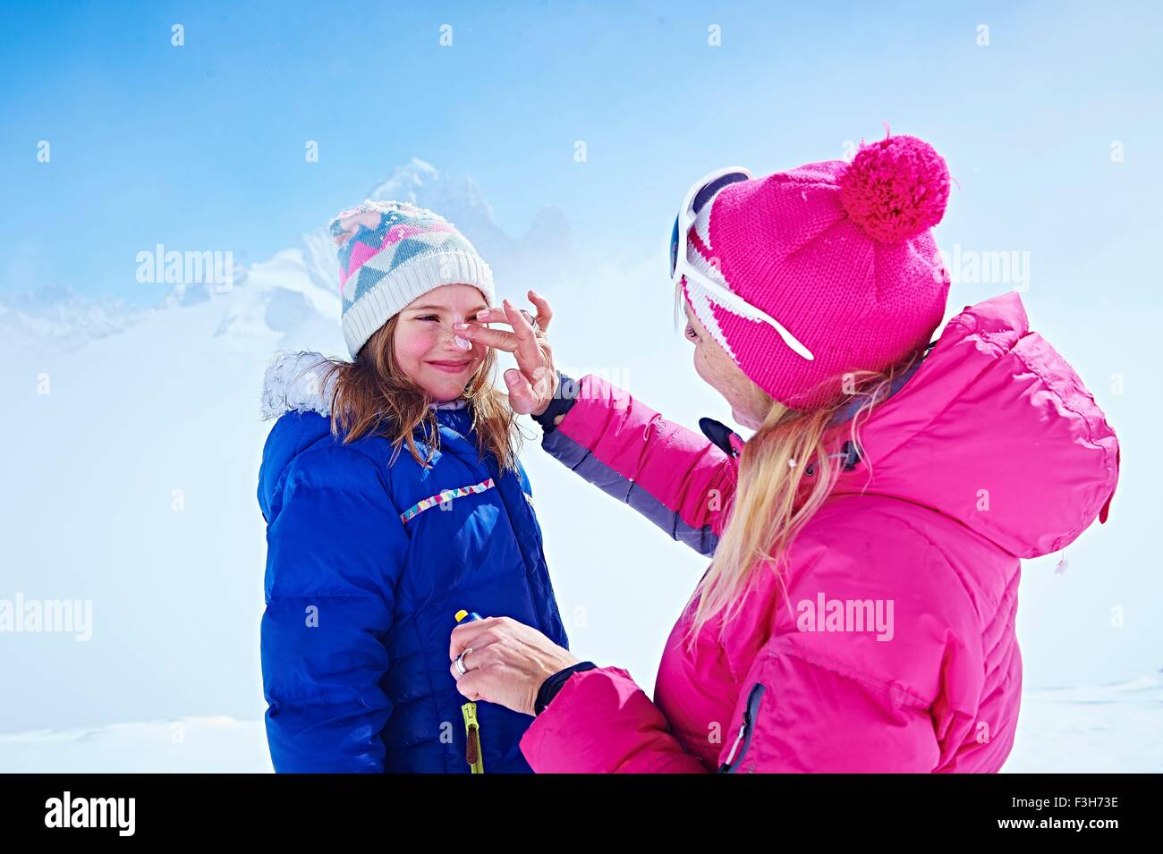 Mother applying sun cream on daughter's face, Chamonix, France - Stock Image